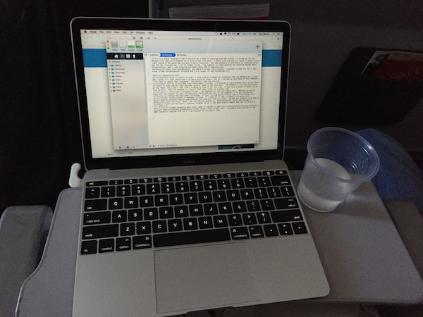 Macbook on a folding tray table in coach